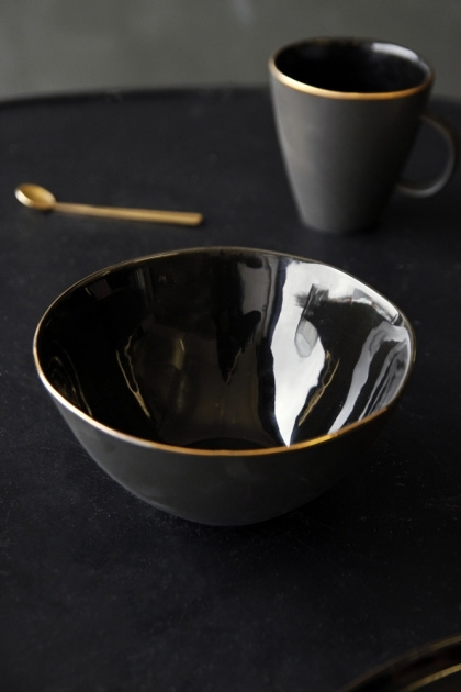 lifestyle image of Glossy Noir Bowl With Gold Rim with mug and spoon on black table