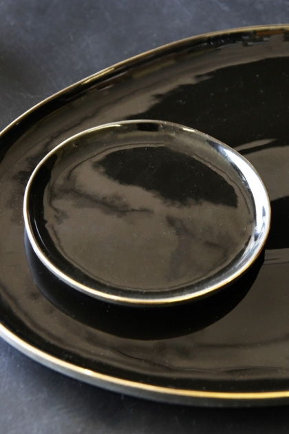 lifestyle image of Glossy Noir Muffin Plate With Gold Rim on large plate and black table