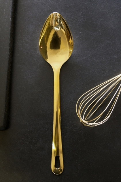 lifestyle image of Gold Kitchen Utensil - Spoon with gold whisk in corner and on black table background