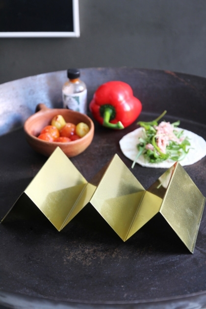 lifestyle image of Gold Metal Kitchen Stand on black table with red pepper and other foods