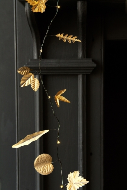 lifestyle image of Gold Metal Leaf Garland Light Chain with black fire place in background