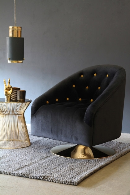 lifestyle image of Gold Spot Black Velvet Swivel Tub Armchair on grey rug with gold side table under black and gold ceiling light and grey wall background