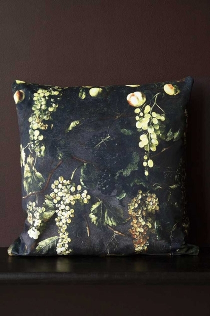 Lifestyle image of the Grape Vine Velvet Cushion on black bench on dark wall background