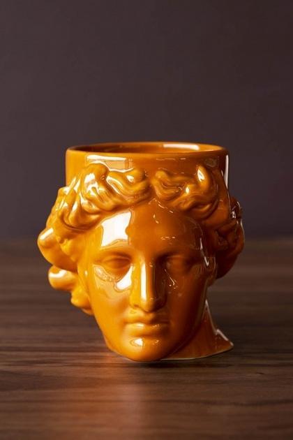 Front-on lifestyle image of the Greek Goddess Hestia Mug in Burnt Orange on dark wooden surface and dark wall background