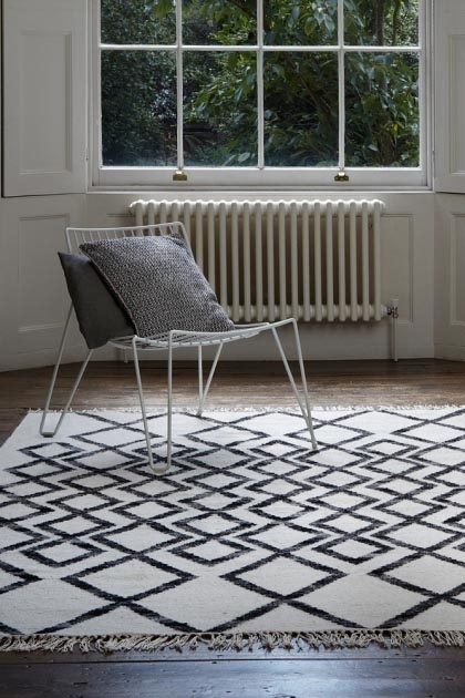 lifestyle image of Hackney Diamond Kelim Rug - Various Colours & Sizes with white wire chair with grey cushions and window in background