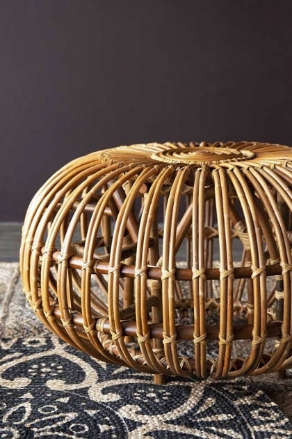 Front on lifestyle image of the Handmade Woven Wicker Pouffe on mandala rug and dark wall background