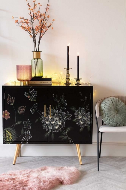 Lifestyle image of the Hand-Painted Dark Florals Sideboard on a white background with accessories & light on