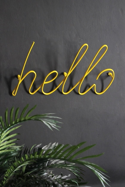 lifestyle image of Hello Wall Art / Hanger - Yellow with plant on grey wall background
