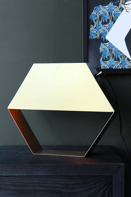 lifestyle image of Hexagonal Brass Table Lamp turned off and upside down on black table with art on wall in background