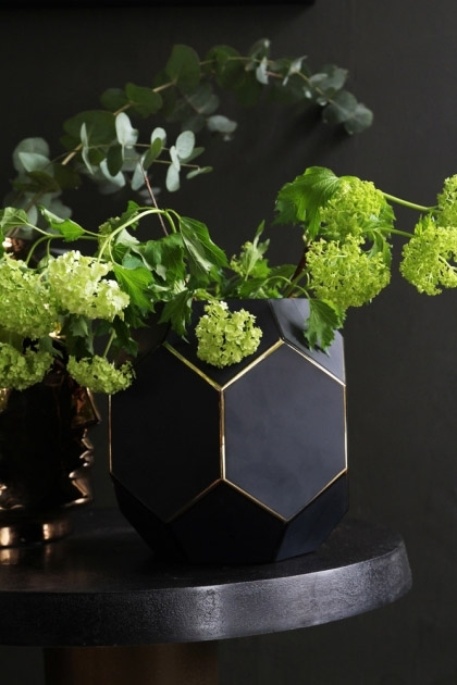 lifestyle image of Honeycomb Jewel Vase - Black with green flowers in on black side table