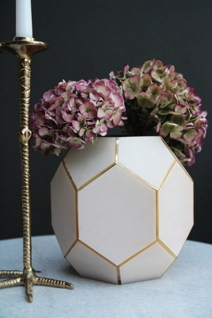 lifestyle image of Honeycomb Jewel Vase - Rose Pink with pink flowers in and candlestick on white table with dark wall background