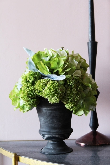 lifestyle image of Hydrangea & Sedum Floral Arrangement In Grey Pot on black table with black candle stick and pink wall background