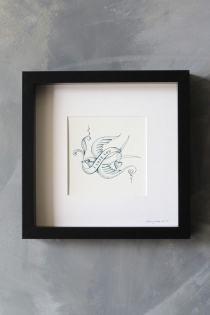 lifestyle image of I Love You Bird Tattoo Art Work By Brigitte Herrod in black square frame on distressed grey wall