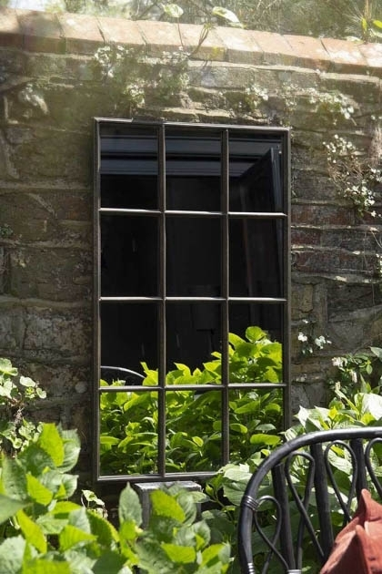 Lifestyle image of the Indoor Or Outdoor Crittall Mirror on dark brick wall in outside setting