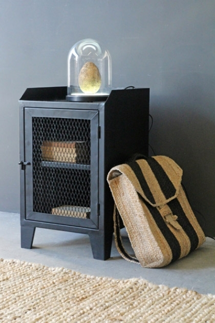 lifestyle image of Industrial Bedside Table with books inside and glass dome on top with backpack leaning against it with rattan rug and dark grey wall background