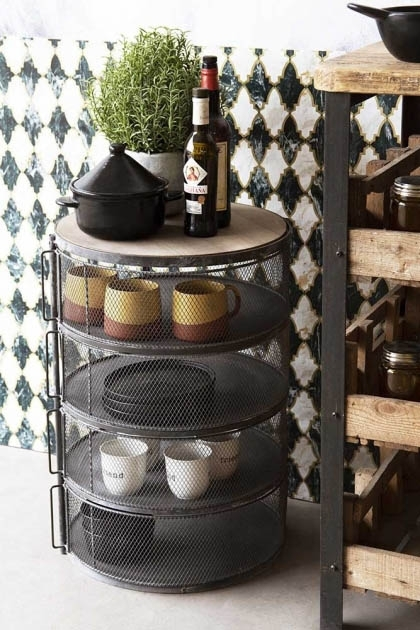 Lifestyle image of the Industrial-Style 4-Shelf Barrel Mesh Storage Cabinet filled with kitchen tableware with plants and a patterned wall background