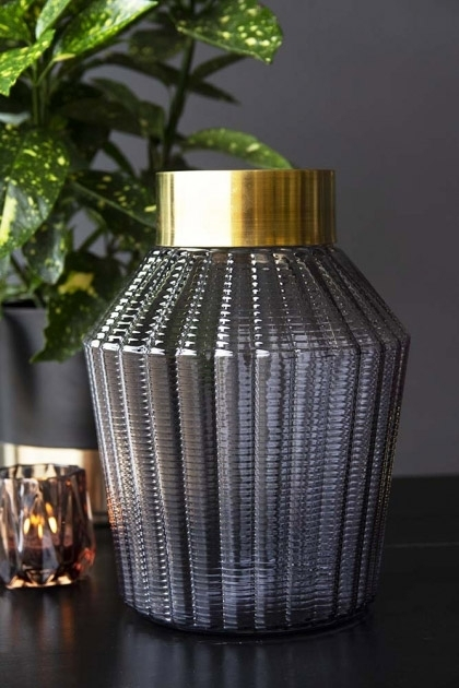 lifestyle image of Ink Ribbed Glass Vase With Gold Top with tea light holder and plant on black table and dark wall background