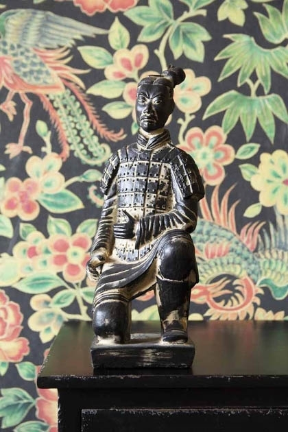 Lifestyle image of the Kneeling Qin Dynasty Figure Ornament on black side table with Rockett St George Oriental Garden Wallpaper in background