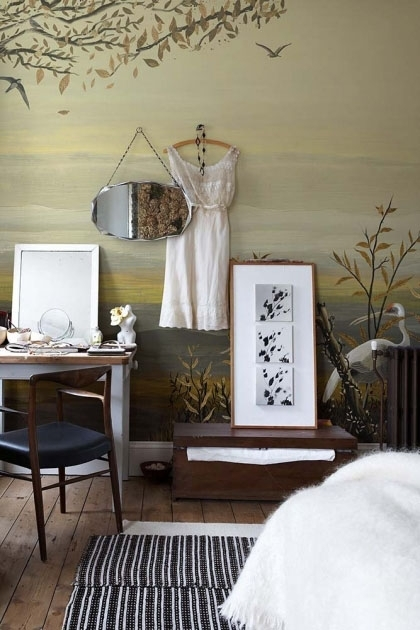 Lifestyle image of the Landscape Wallpaper Mural - Yugure Chai with dress and mirror hanging on wall and table in corner with patterned rug on floor and brown chest with picture frame leaning on wall on top