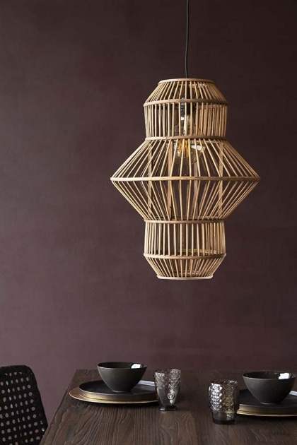Lifestyle image of the Lantern Shape Bamboo Pendant Light over dining table with tableware and chair with dark wall background