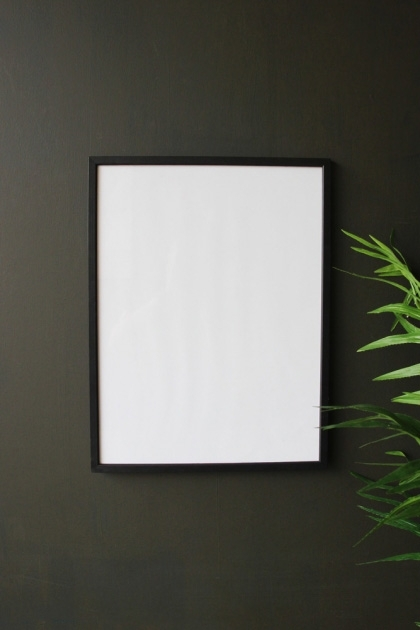 lifestyle image of Large Black Wooden Frame - 30cm X 40cm with plant on dark grey wall background