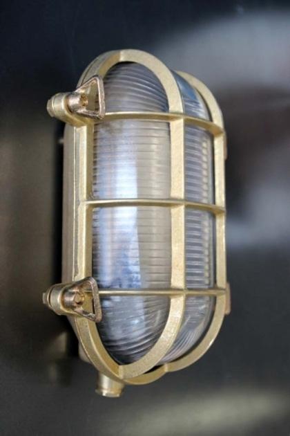 Vintage brass oval bulkhead light on a metal wall lifestyle image