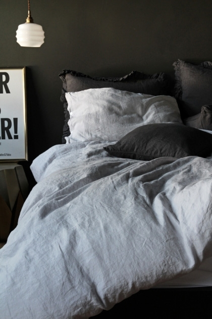 lifestyle image of Lisbon Soft Linen Duvet Cover - Silver Grey with grey and white pillows and white ceiling light above black and white typography print and grey wall background
