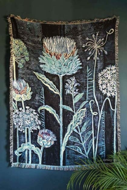 lifestyle image of Lucy Tiffney Stunning Allium Cotton Throw hanging on dark grey wall with house plant in corner
