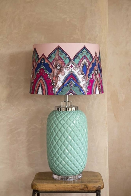 Lifestyle image of the Matthew Williamson Jaipur Jewel Indian Table Lamp & Shade on wooden side table and pale textured wall background
