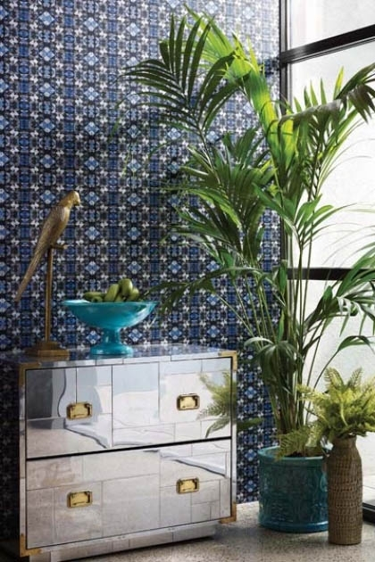 lifestyle image of Matthew Williamson Mustique Wallpaper with mirrored chest of drawers and large plant