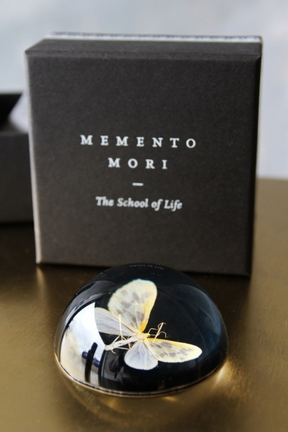 lifestyle image of Memento Mori Paperweight - Moth Print with box on gold table