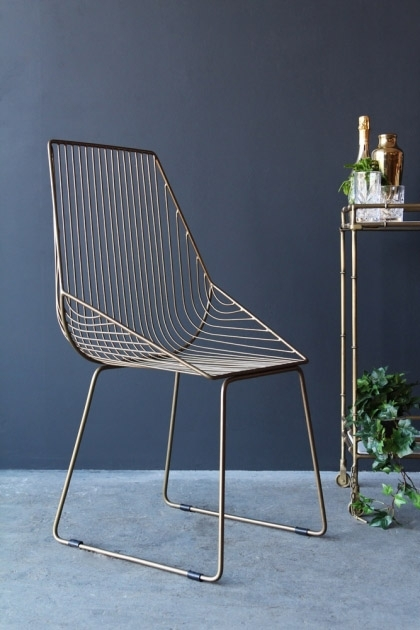 lifestyle image of Midas Chair with gold drinks trolley on grey flooring and dark wall background