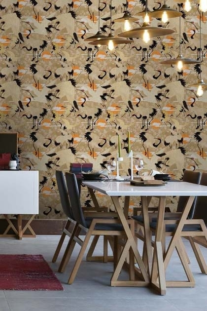 Lifestyle image of Birds of Happiness wallpaper with white and wooden dining table with black dining chairs and red rug on floor