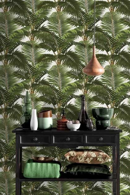 lifestyle image of Mind The Gap Jardin Tropical Wallpaper with wooden ceiling light and black storage unit filled with cushions and vases on top