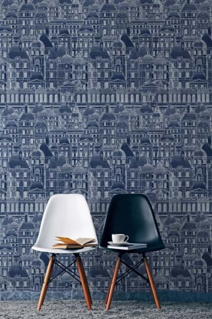 lifestyle image of Mind The Gap Wallpaper Collection - Louvre - Blue with black and white dining chairs with books and mug on top