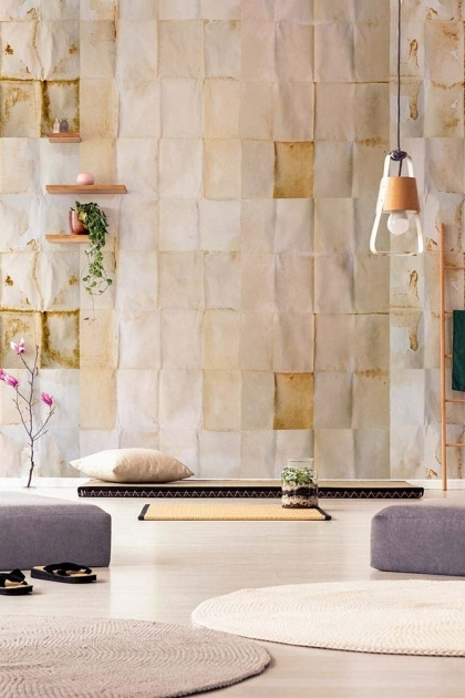 Lifestyle image of the Shibui wallpaper in natural with ceiling light hanging from ceiling and shelves on the wall and round rugs in foreground