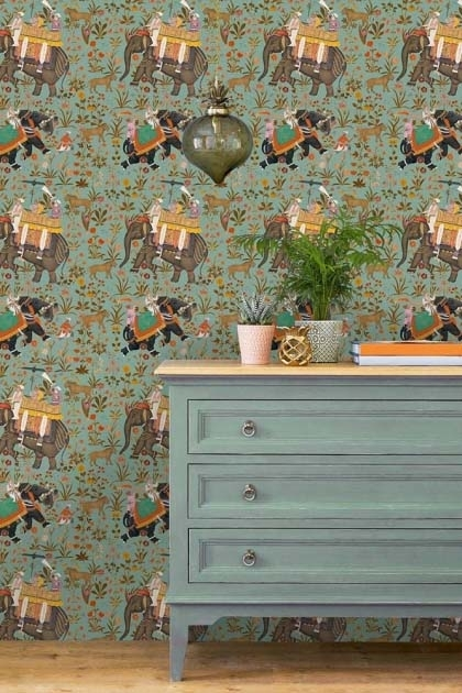 lifestyle image of Mind The Gap The Mysterious Traveler - Hindustan Wallpaper - Aquamarine with blue chest of drawers with plant and ornaments on top
