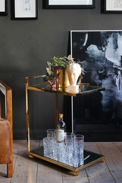 lifestyle image of Mirrored Glass Drinks Trolley with glasses and gold plant pot and bust with leather chair and large black painting on floor