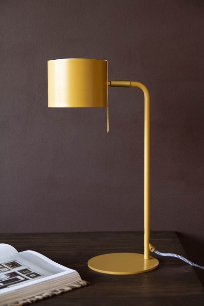 Lifestyle image of the Modern Gold Accent Table Lamp - Ochre Gold on dark table with book on dark wall background