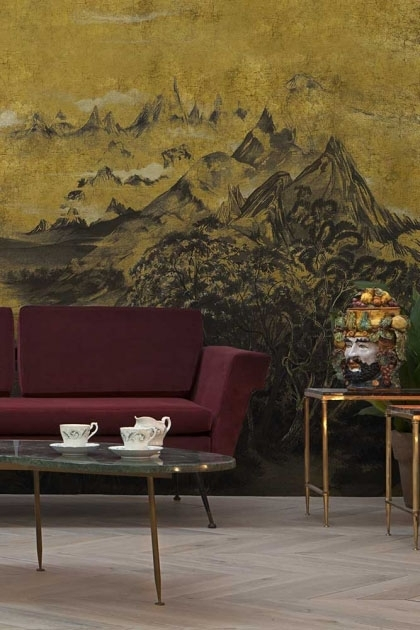 Lifestyle image of the Mountains Wallpaper Mural - Kami Chai with purple sofa and glass coffee table with tea cup and side table with vase on top in background