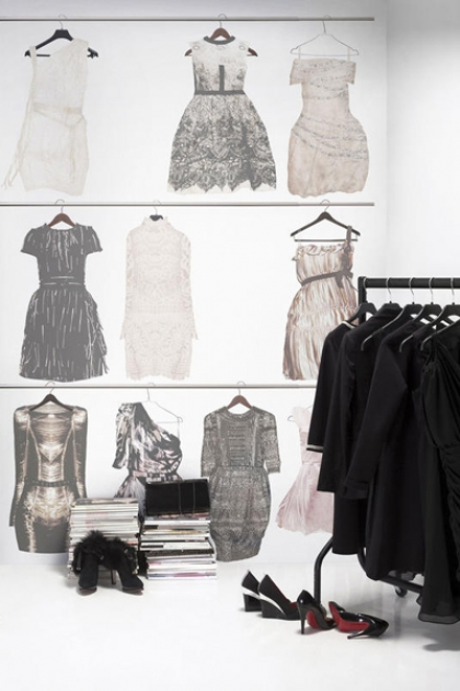 Lifestyle image of Mr Perswall Wallpaper - Fashion Collection - Walldrobe with black clothes rack with black clothes hanging on it and pile of magazines