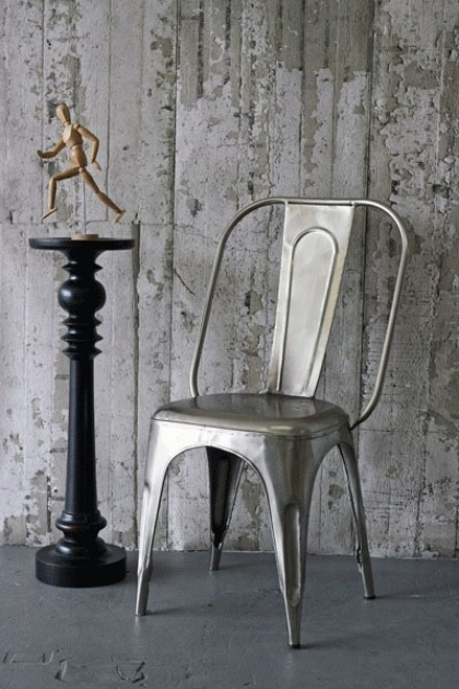 lifestyle image of NLXL CON-06 Concrete Wallpaper by Piet Boon with metal chair and black side table with wooden man ornament