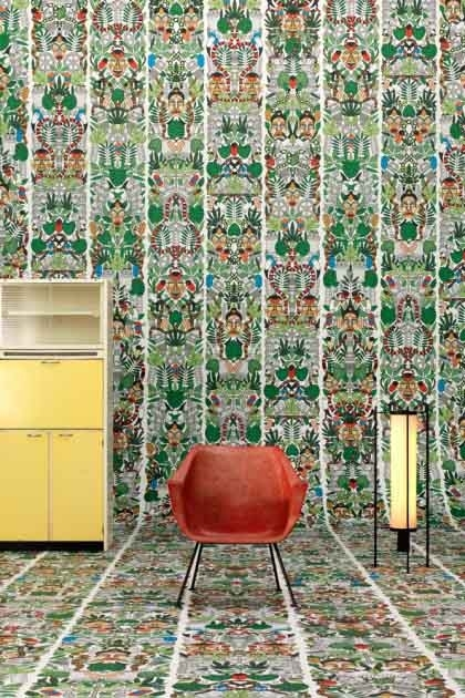 lifestyle image of NLXL JOB-05 L'Afrique Archives Wallpaper by Studio Job on wall and floor with orange brown chair, black lit up lantern and yellow drawer unit