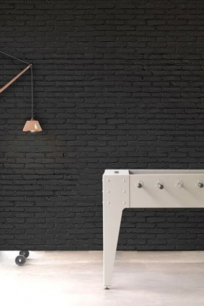 lifestyle image of NLXL PHM-33 Black Brick Wallpaper By Piet Hein Eek with white football table and copper effect light