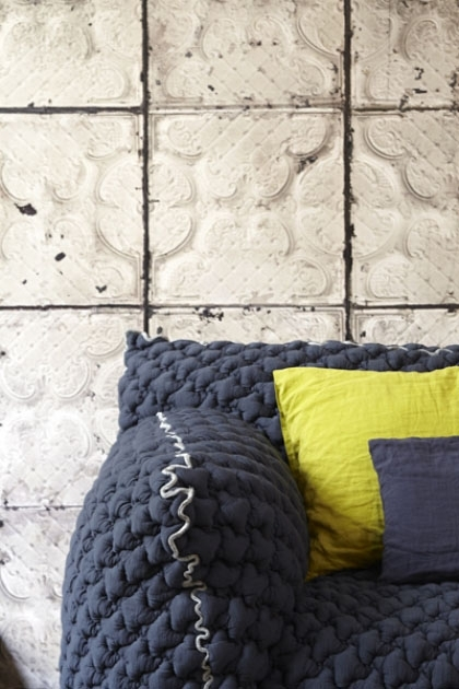 lifestyle image of NLXL TIN-03 Brooklyn Tin Tiles Wallpaper By Merci with grey sofa and yellow and grey cushions