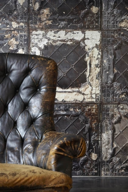 lifestyle image of NLXL TIN-07 Brooklyn Tin Tiles Wallpaper By Merci with leather armchair
