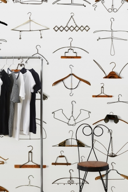 Lifestyle image of NLXL DRO-02 Obsession Wallpaper by Daniel Rozensztroch - Hangers with small wooden stool and metal clothing rack with clothes hanging on it
