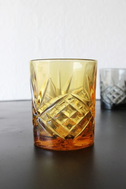 lifestyle image of Old Fashioned Crystal Style Tumbler - Amber on black table with pale wall background