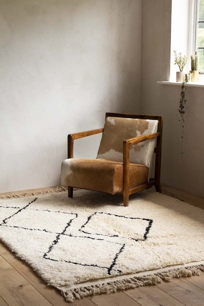 Lifestyle image of the Original Moroccan Berber Large Rug wih cowhie armchair on pale wooden floor and pale wall background