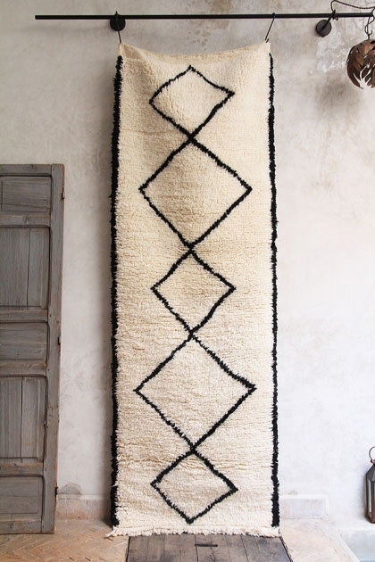 lifestyle image of Original Moroccan Berber Runner - Kasbah hanging on pale wall with grey door next to it